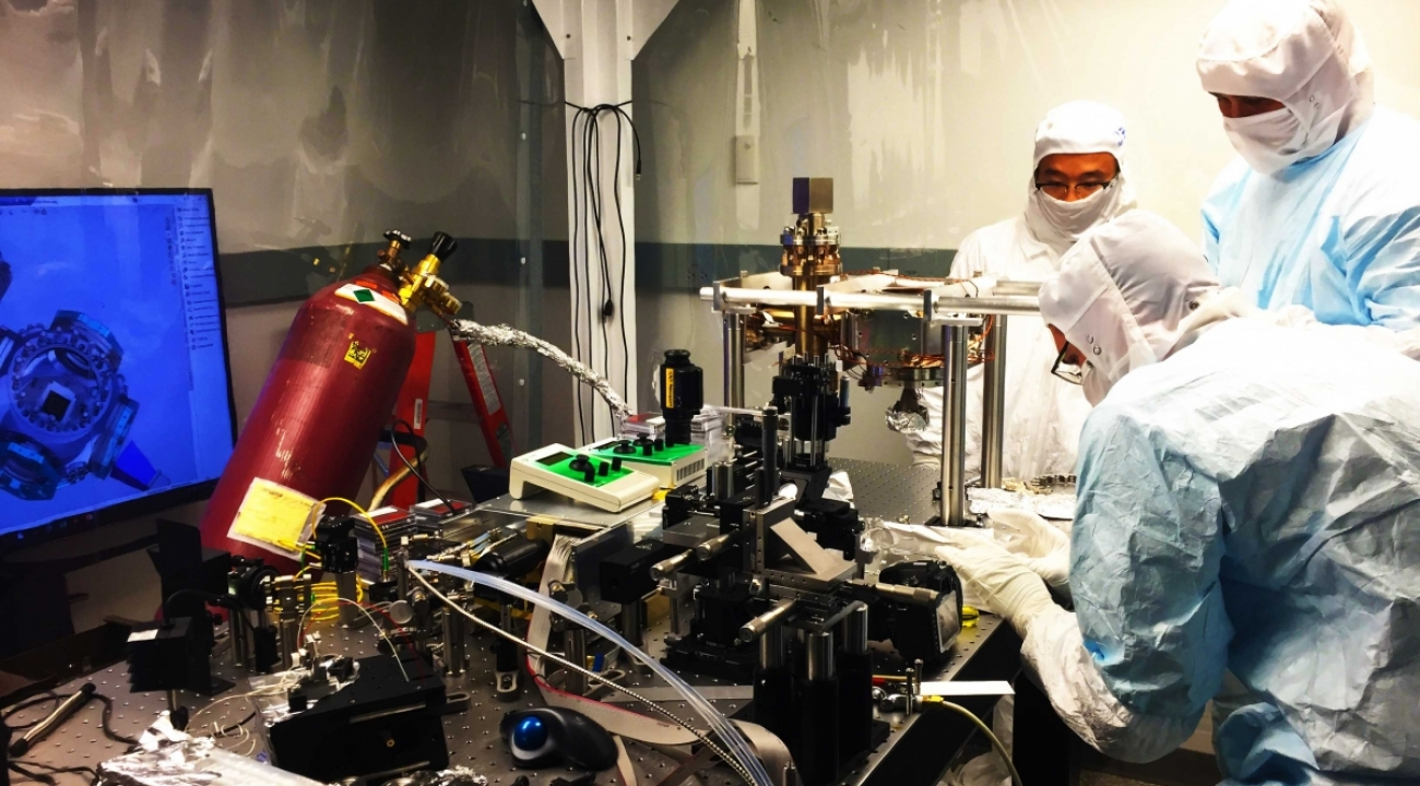 Twentieth international summer school on vacuum electron and ion - Marko Centina Kai Hudek And Daiwei Zhu Assembling An Ion Trap Vacuum System In A Clean Room Their Suits Prevent Contaminants From Entering The Apparatus