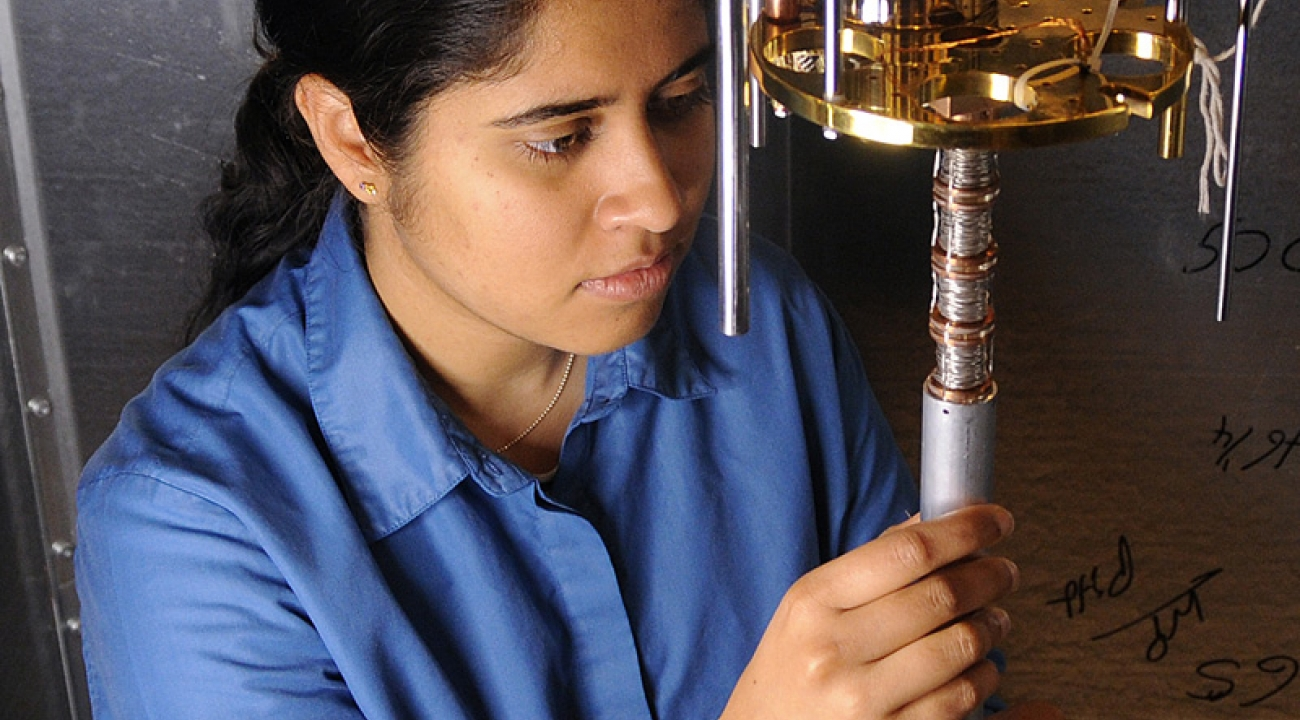 Grad student Anita Roychowdhury examines a dilution refrigerator for cooling the STM device.
