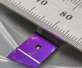 In the cut-out area of the purple mount, a silicon nitride membrane (which measures 1.2 mm X 1.2 mm) holds an array of gratings