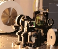 Part of the lab set-up shows photonic crystal (left, red dot) in center of cryogenic enclosure (white). An infrared beam coming from the right is directed through a beamsplitter (cube, center) to the crystal.