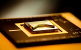 A chip made of golden bow-tie-shaped structure on top of a dark rectangular base that is used to contain ions for experiments and quantum computing tasks. The base of the chip has illegible markings on it.